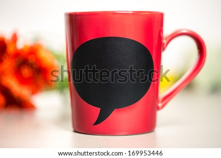 Red ceramic cup with empty chalk board. Standing on a kitchen table.  - stock photo