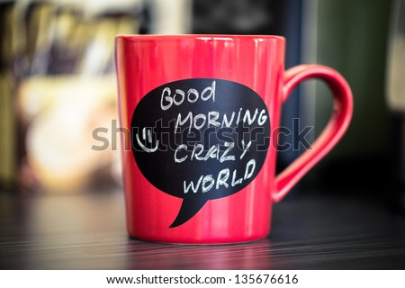 Red ceramic cup with good morning sign made with chalk. Standing on a kitchen table. - stock photo