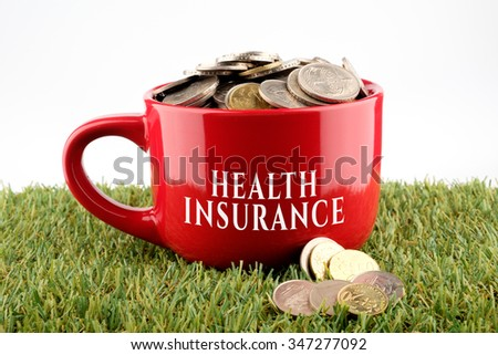 Red ceramic cup written Health Insurance  with coins inside, finance conceptual. - stock photo