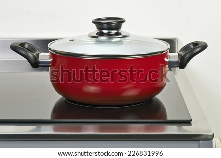 Red ceramic pan with cover on Electric hob in modern and domestic kitchen - stock photo