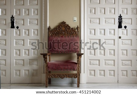 red chair between white doors in a palace