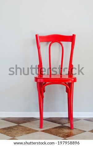 Red Chair on Tiled Floor and Near Grey Wall, indoor - stock photo