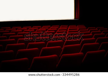 Red chairs in empty cinema theater with empty stage. Light illumination of the stage. Soft light. - stock photo