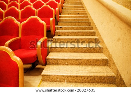 Red chairs in some theater and marble steps - stock photo