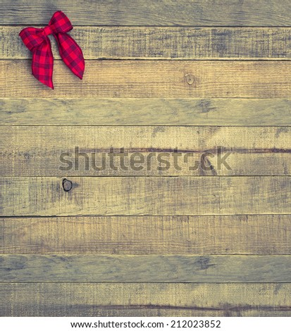 Red Checked Christmas Bow in upper corner on Rustic Wood Board Background with room or space for copy, text, words.  Vintage instagram vertical that can be cropped to horizontal - stock photo