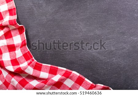 red checkered tablecloth on dark background, top view with copy space