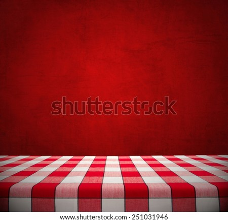 Red checkered tablecloth on dining table against red chalkboard, valentine background - stock photo