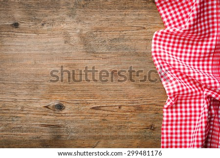 Red checkered tablecloth on wooden table - stock photo