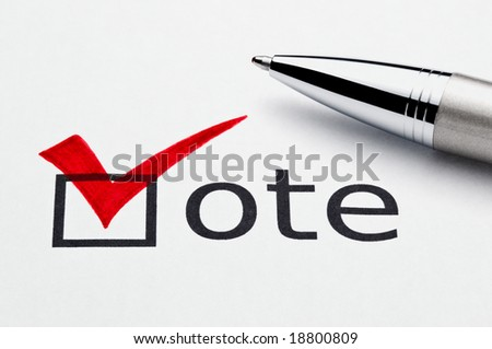Red checkmark on vote checkbox, pen lying on ballot paper. Concept for voter registration and participation in elections, or for voting red/republican; not an isolation, paper texture is visible