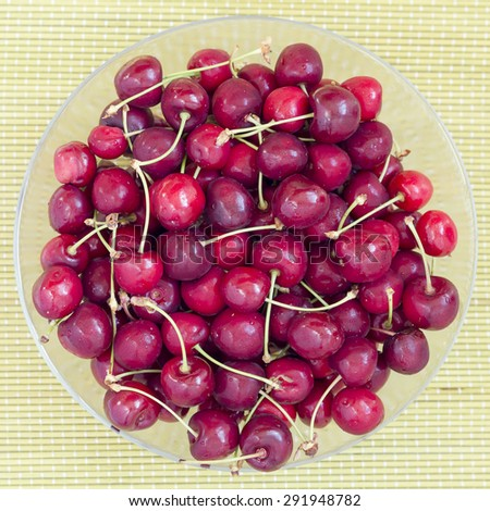 Red cherries fruit in a glass bowl, top view. - stock photo