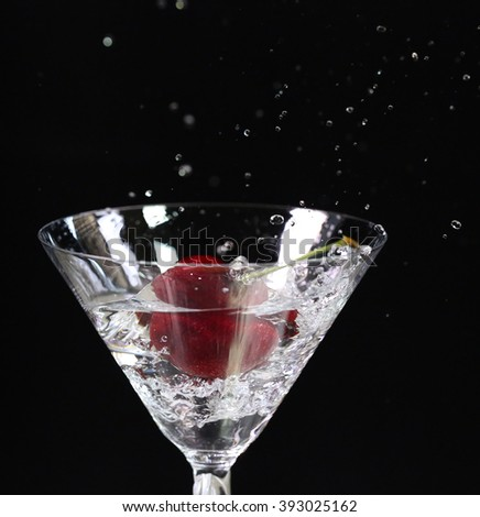 Red cherry fall into the water glass on black background