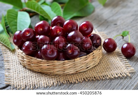 Red cherry in wicker basket on wooden table - stock photo