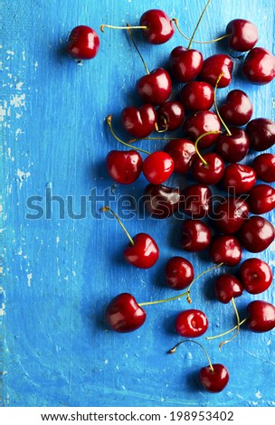 Red cherry on a blue rustic table - stock photo