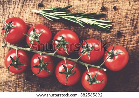 Red cherry tomato branch on rustic wooden table, table top view  - stock photo