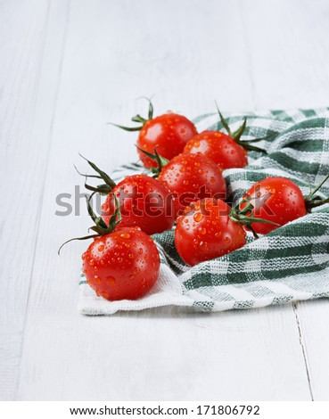 Red cherry tomatoes in water drops on a green linen napkin on a white colored wooden surface