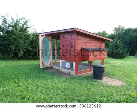 red chicken coop made of wood and metal screen         - stock photo