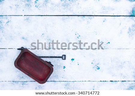 Red child's wagon on rustic teal blue snowy wood background - stock photo