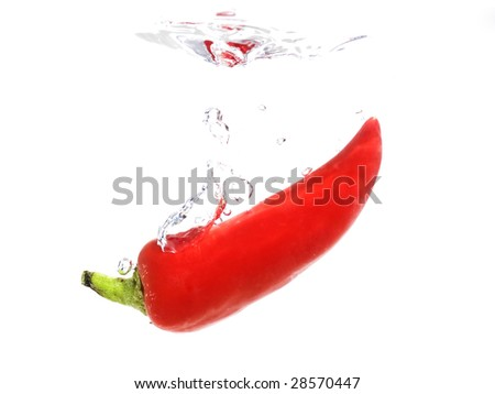 Red chili dropping into water - stock photo
