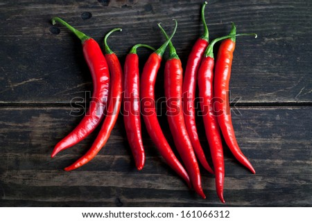 Red chili pepper on the wooden desk - stock photo
