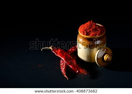 Red Chili Pepper powder in clay pot with Red Chili Peppers on black background - stock photo