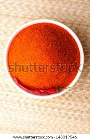 Red Chili pepper with pile of milled peppers  - stock photo