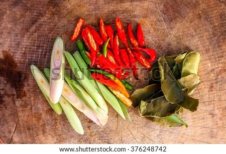 Red chili peppers and lemongrass on the wooden table