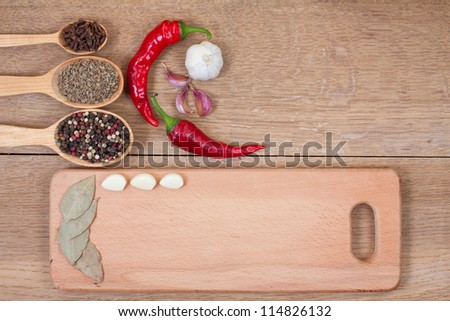 Red chili peppers, garlic, bay leaf, spices in spoon and kitchen board on oak wood texture background