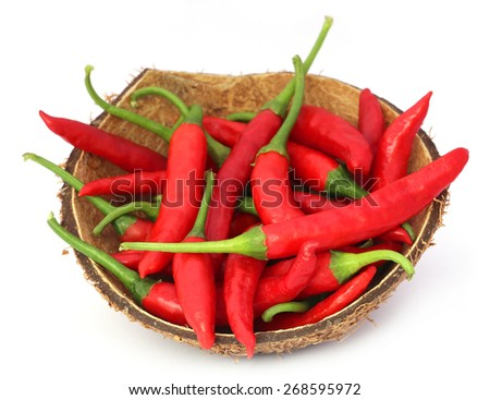 Red chili peppers in a coconut shell over white background - stock photo