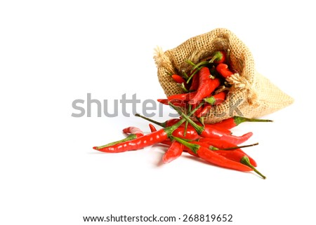Red chili peppers in a sack bag on white background. - stock photo