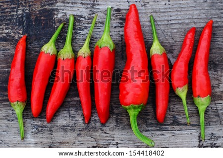 Red chili peppers on an old wooden background - stock photo