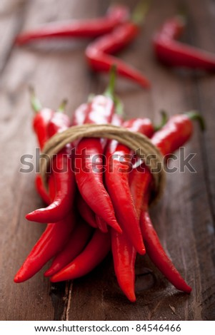 Red Chili Peppers Tied with Rope on Wood - stock photo