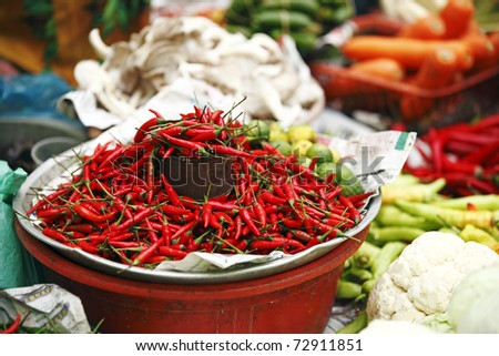 Red chilli pepper of the Asian Chilli Padi specimen being sold by measurement of a tin can on display in an exotic wet market in Kota Bahru, Kelantan, Malaysia. - stock photo
