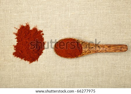 Red chilli spice on bamboo spoon on brown background, top view. - stock photo