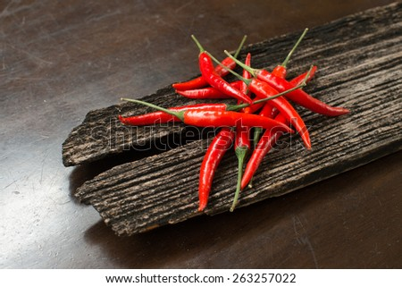 Red chillies on a plank on a table - stock photo