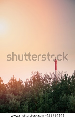 Red chimney growing out of trees  - stock photo