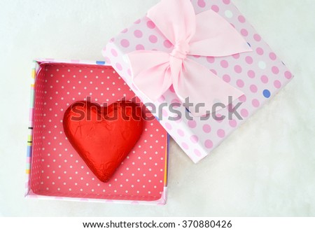 red chocolate candy heart shape and gift box on snow background