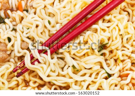 red chopsticks on cooked instant ramen close up - stock photo