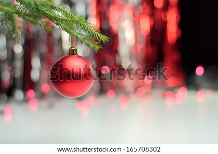 Red christmas ball hanging on the pine branch - stock photo