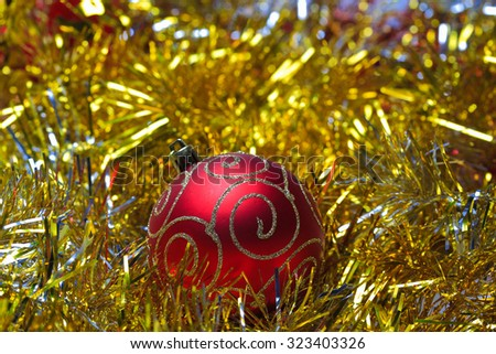 Red christmas ball in the golden tinsel defocused blur backgrounds - stock photo
