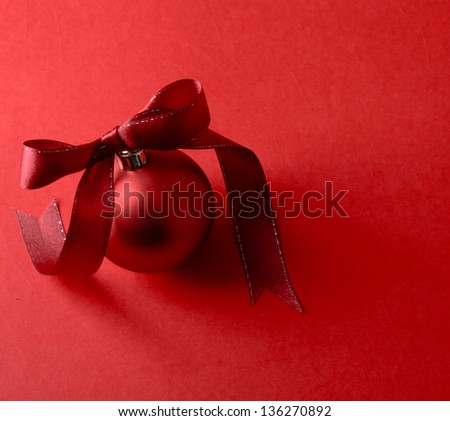 Red christmas ball, isolated on red background - stock photo