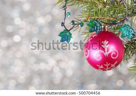 Red Christmas ball on a Christmas tree branch over blurred shiny background, close up. Selective focus.