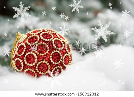red christmas ball on fir tree with snow - stock photo