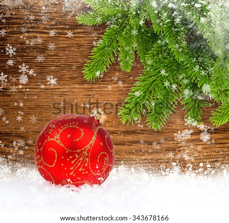 Red christmas ball on snow with spruce twigs on wooden background - stock photo