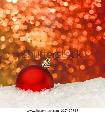 Red christmas ball on the defocused background of blurred Christmas lights at night - stock photo