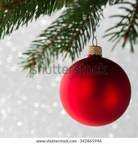 Red christmas ball on the xmas tree on glitter bokeh background. Merry christmas card. Winter holidays. Xmas theme. - stock photo