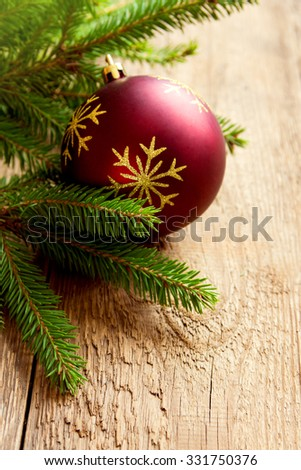 Red Christmas ball on wooden background with branches of green fir, copy space - stock photo