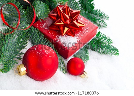 red Christmas ball with pine branch, gift and snow, on white snow background - stock photo