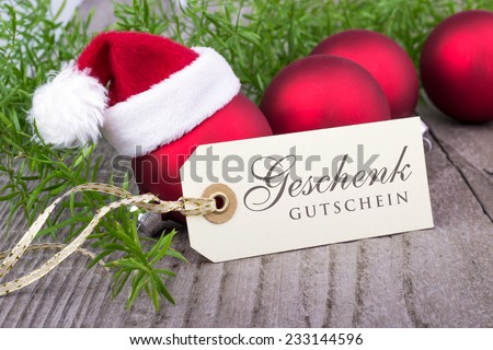 red christmas balls and card with german text gift card/gift card/german - stock photo