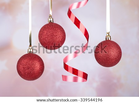 Red Christmas balls and ribbon hanging against a colorful background - stock photo