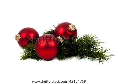 Red Christmas balls/baubles with a pine tree branch on a white background - stock photo